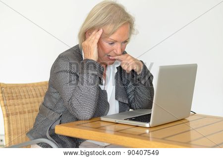 Active Blond Senior Woman With Formal Clothes Sitting Thoughtful At A Desk In Front Of A Silver Lapt