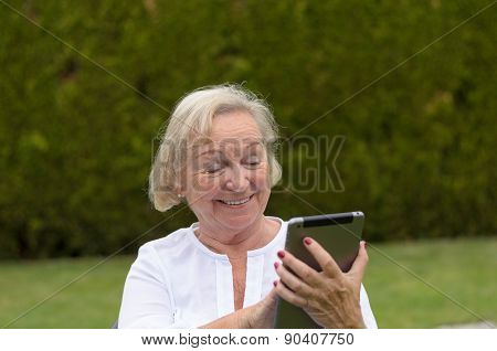 Senior Serene Woman Using A Black Tablet Pc