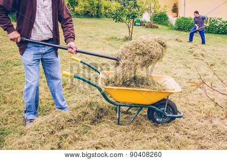 Men working hard raking dry hay on field