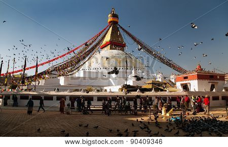 Bodhnath Stupa With Tourists, Buddhist Monks And Pigeons