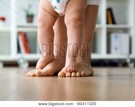 Mother And Baby Legs. First Steps.