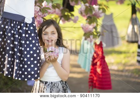 Little Girl Among Dresses In The Tree