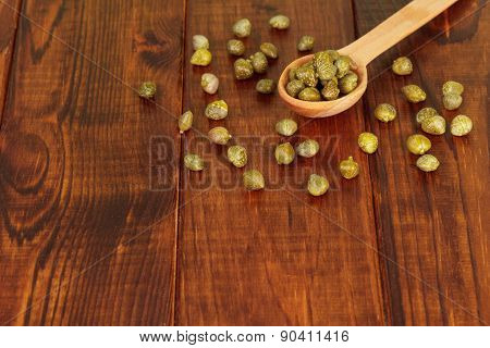 Green capers in spoon