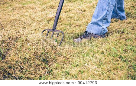 Senior man feet raking hay with pitchfork on field