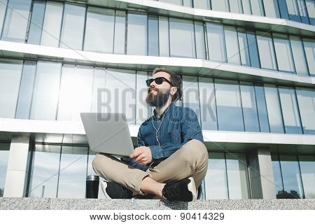 Businessman In Sunglasses With Laptop Outdoors In Front Of Office