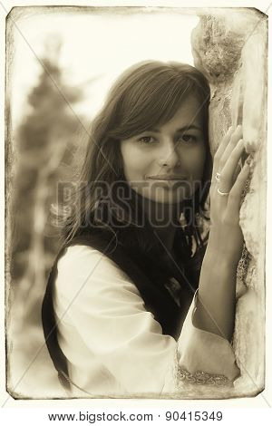 beautiful young woman with long dark hair and a historical dress at a rough ancient stone wall