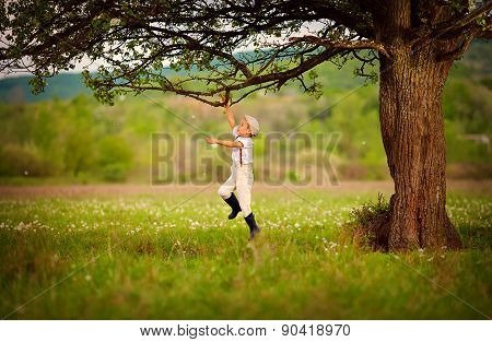 Cute Little Farmer Boy Playing Under An Old Tree
