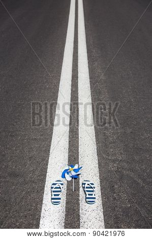 Holiday slippers with pinwheel lying on asphalt