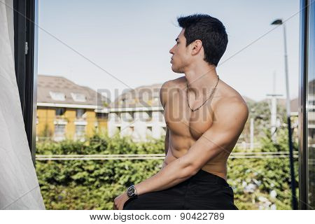 Handsome young man shirtless sitting on window ledge