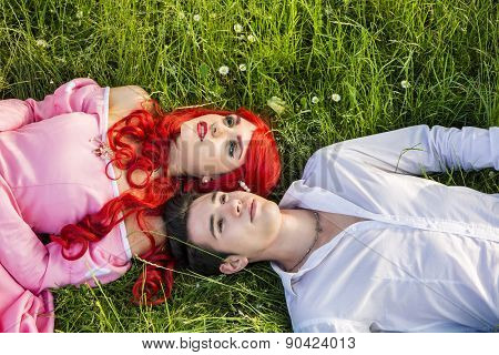 Romantic Fairy Tale Couple Sitting in Garden among Flowers