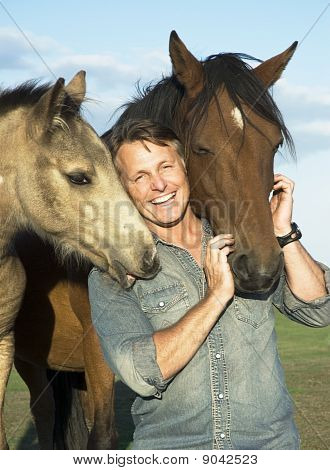 happy smiling man with his horses