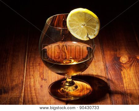 Glass of cognac with lemon