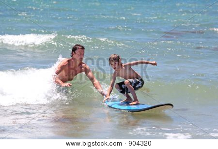 Father Teaching His Young Son To Surf