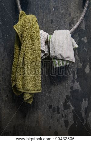 Hanging towel and cottons on shower wire with old dirty wall