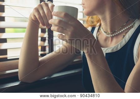 Woman Having Coffee By The Window In A Diner