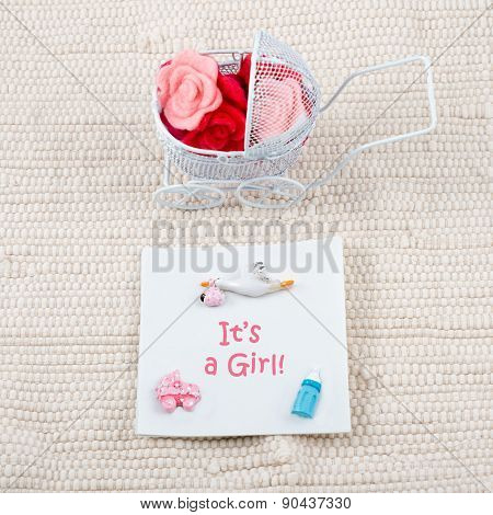 Baby card - Its a girl theme. Pram full of flowers on white textile background. Newborn greeting car