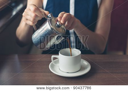 Young Woman Pouring Coffee In Diner