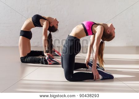 women warming up arching stretching their backs holding legs and working out in a gym yoga class