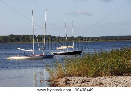 Sailboats Moored In Front Of A Natural Beach.