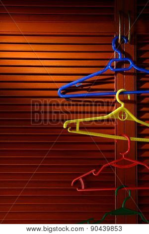 Wooden cabinet door with linked hangers on its metal handle