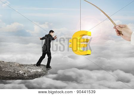 Man Balancing Golden Euro Symbol Fishing Lure With Sun Clouds