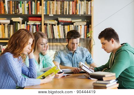 people, knowledge, education and school concept - group of students reading books and preparing to exam in library