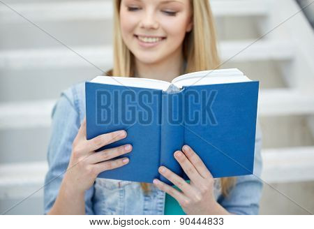 school and education concept - close up of happy young woman reading book at school