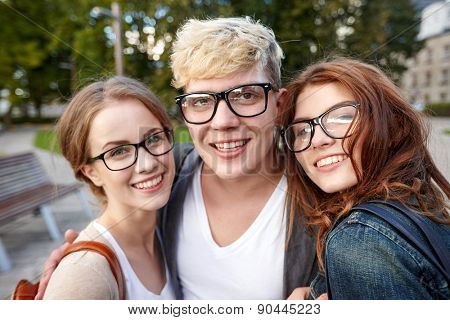 education, friendship, eyesight and teenage concept - group of happy teenage students in eyeglasses at campus