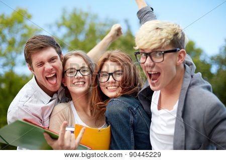education, friendship, success and teenage concept - group of happy students showing triumph gesture at campus or park