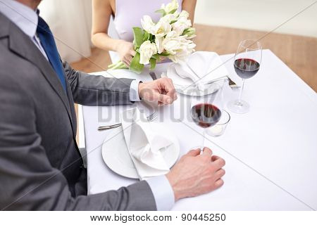 restaurant, people, celebration and holiday concept - close up of young couple with tulip flowers and glasses of red wine at restaurant