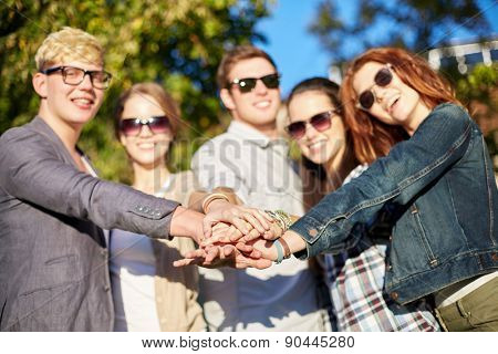 friendship, togetherness, team and people concept - close up of teenage friends in sunglasses with hands on top