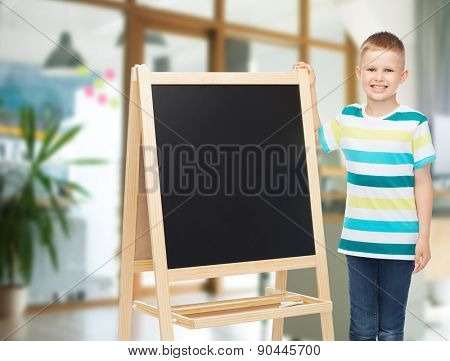 people, advertisement, children and education concept - happy little boy with blank blackboard over school class room background
