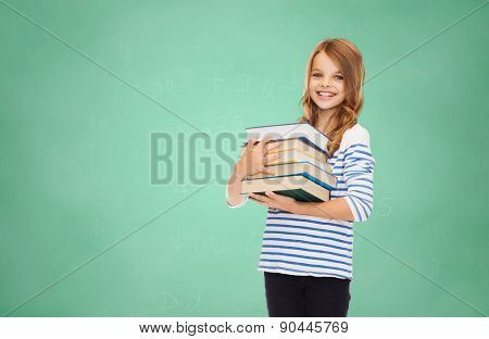 education, people, children and school concept - happy little student girl with many books over green board background