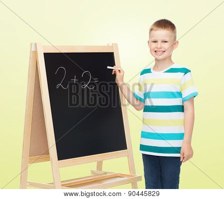 people, school, children, mathematics and education concept - happy little boy with blackboard and chalk writing math exercise over yellow background