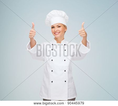 cooking, gesture and food concept - smiling female chef, cook or baker showing thumbs up over gray background