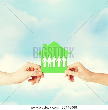 real estate and family home concept - isolated closeup picture of male and female hands holding green paper house