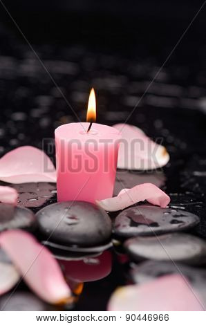 rose petals,candle and wet stones