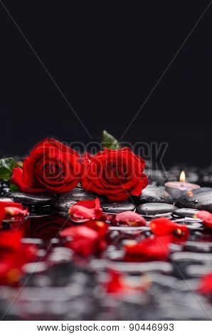 Two red rose with candle and therapy stones
