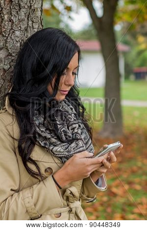 a young woman writes a text message on his cell phone. communication with a smart phone