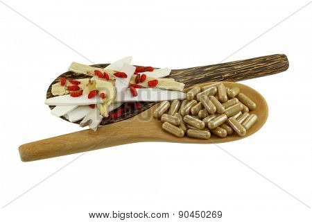 A wooden spoon full of Chinese medical herb and Natural herbal capsules isolated on a white background