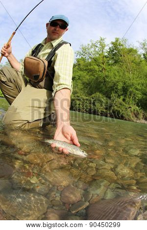 Fisherman catching brown trout with fishing line in river