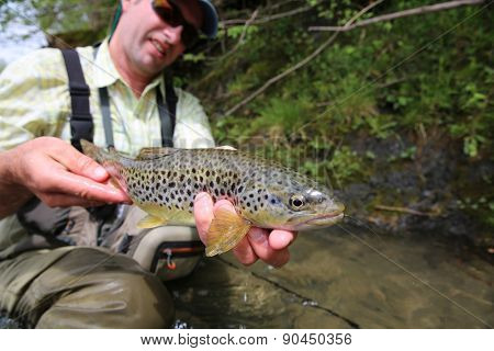 Fisherman holding recently caught brown trout