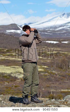 young man using binoculars outdoor