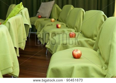 Apples placed on the chairs for each member of the auditorium, focus on the closest apple
