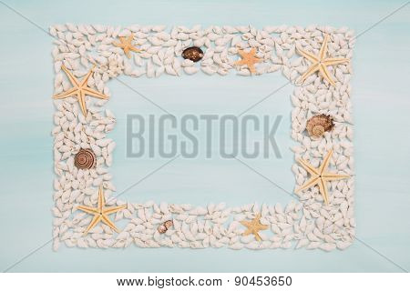 Tropical frame of starfish and shells for maritime decoration in summertime.