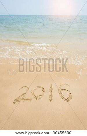 Year 2016 written in sand, on tropical beach