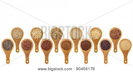 a variety of gluten free grains (buckwheat, amaranth, brown rice, millet, sorghum, teff, black, red, white and black quinoa, chia seeds, flax seeds) on wooden spoons isolated on white