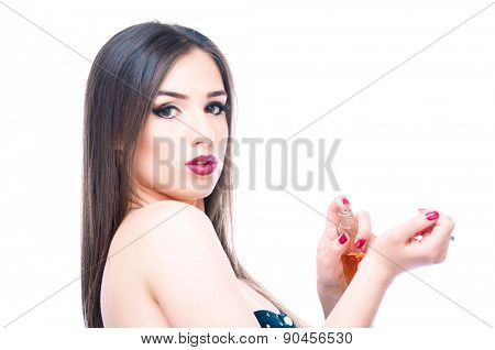 Beautiful girl applying perfume on her hand and looking into camera, isolated on white