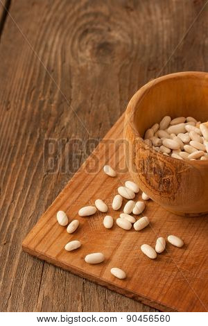 Beans in a wood pot on natural textured wood background. Natural uncooked raw organic food