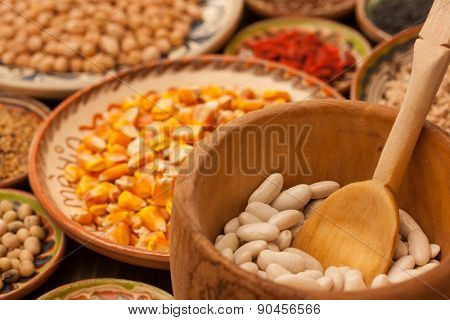 Various grain beans in small clay plates on natural textured wood background. Uncooked organic raw food.